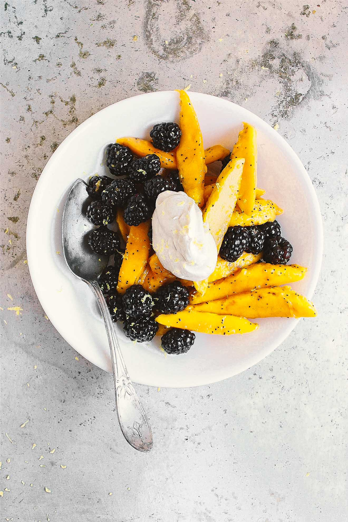 Mango Fruit Salad with Poppy Seed + Earl Grey Coconut Cream | Life-changing mango fruit salad with fresh berries, honey lemon poppy seed dressing and earl grey coconut cream. The best springtime fruit salad. An easy, classy fruit salad dessert to impress.
