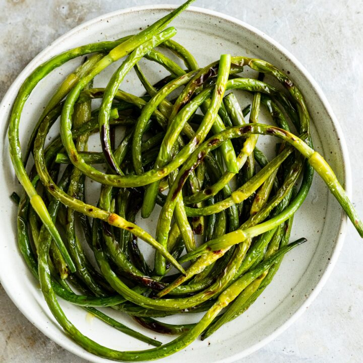 grilled garlic scapes on a plate with salt