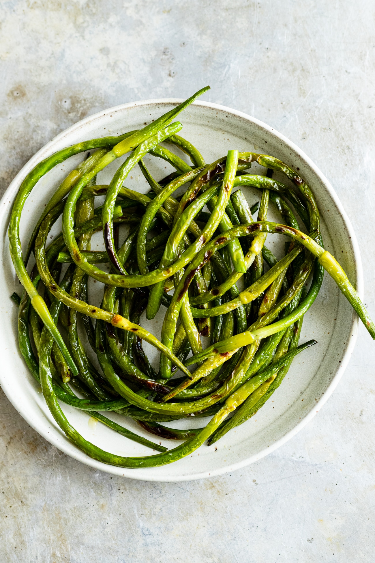 Simple Grilled Garlic Scapes with Salt + Pepper | Simple grilled garlic scapes with olive oil and seasoned with sea salt and pepper. An easy, whole garlic scape recipe. Grilled garlic scapes make a flavorful side dish. #garlicscapes #grilledgarlicscapes