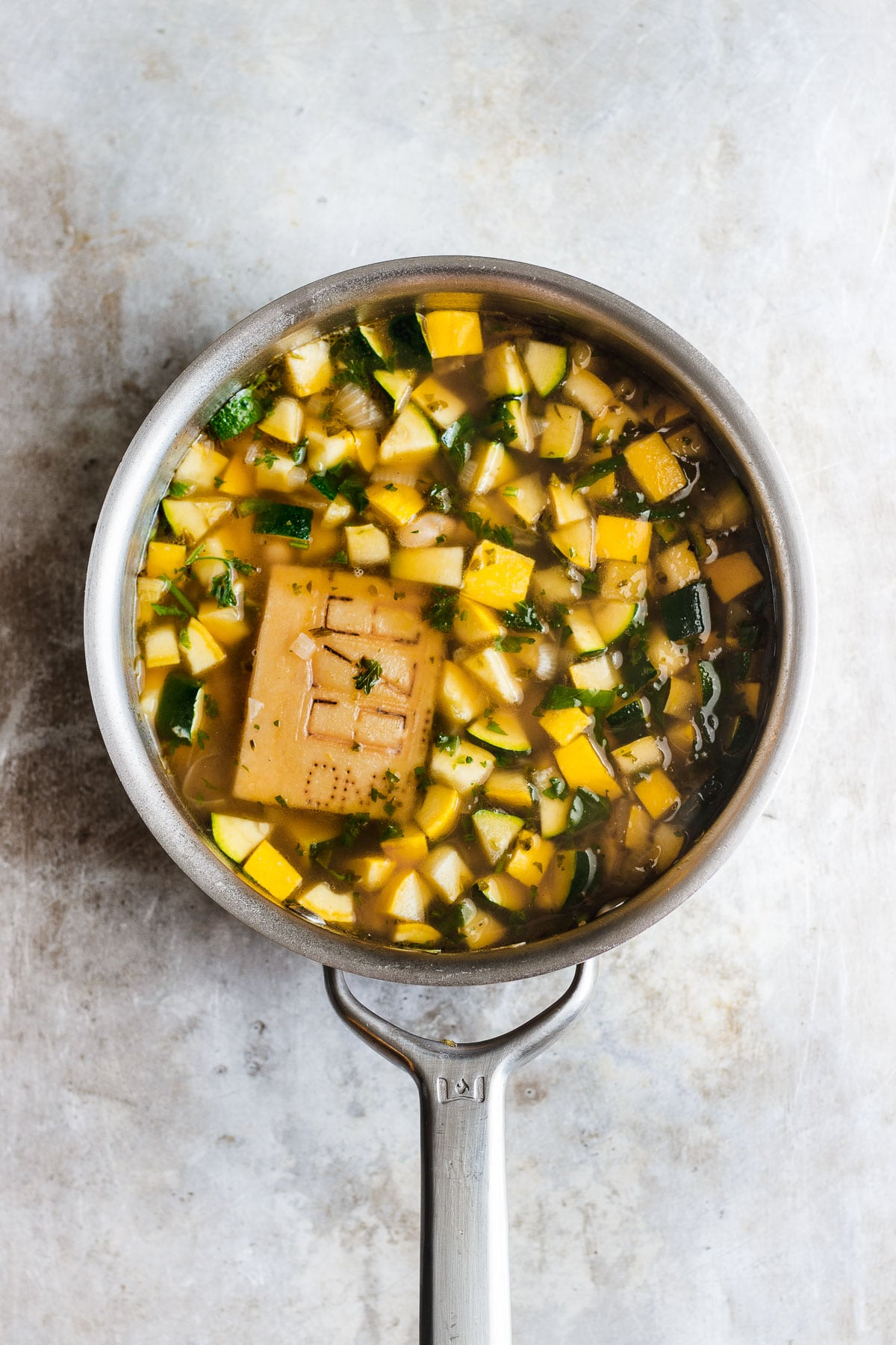 zucchini soup in a pot with parmesan rind