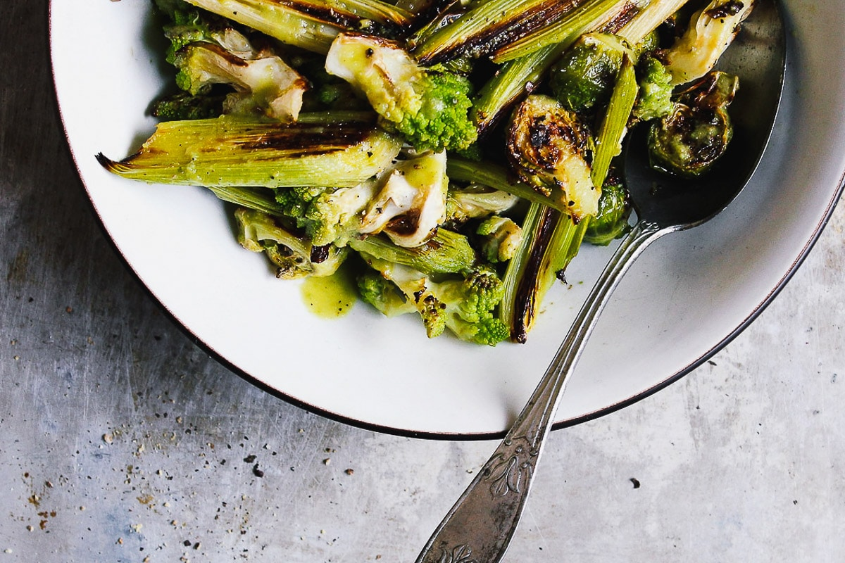 A charred, roasted romanesco salad with brussels and leeks, and tossed in a salty green olive dressing. A warm and hearty salad perfect for fall or winter. #roastedromanesco #romanescorecipes #romanescosalad