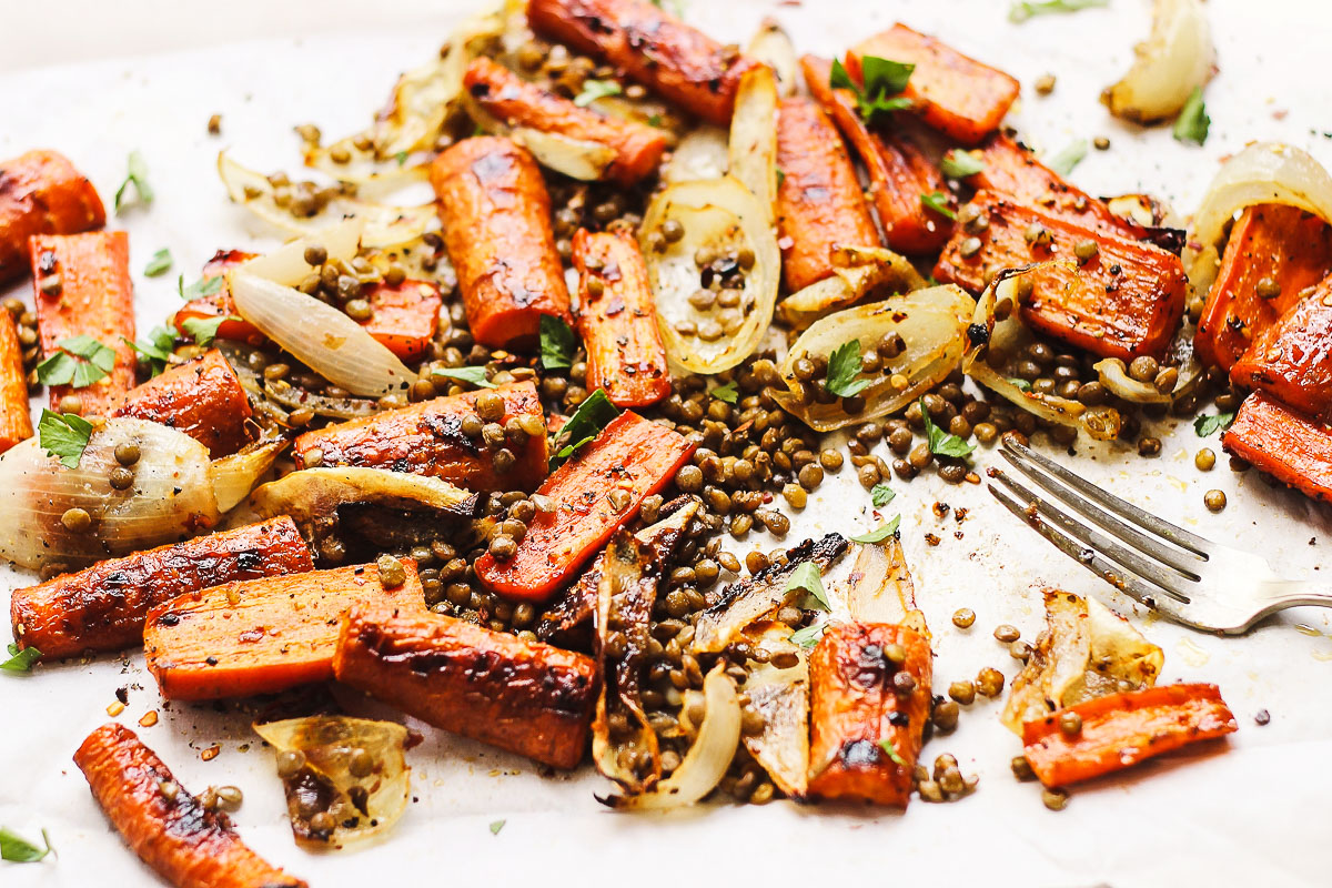 Sweet and spicy maple roasted carrots with crispy lentils and herbs. A cozy, naturally vegan and gluten-free sheet pan meal. #crispylentils #maplecarrots #sheetpanmeals