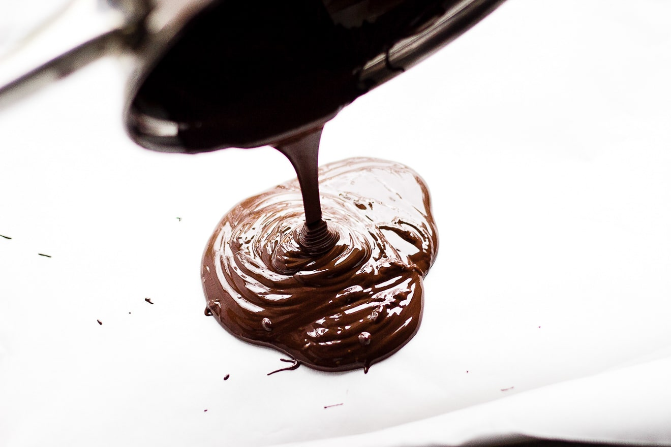 pouring melted chocolate onto tray