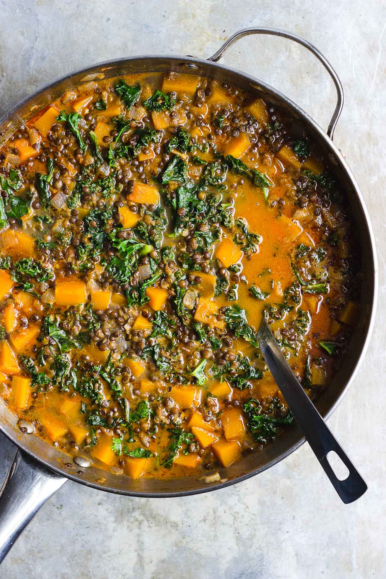 Red Curry Lentil Stew with Butternut Squash + Kale | Red curry lentil stew with butternut squash, kale and creamy coconut milk. It's naturally gluten-free and vegan. It's a hearty fall lentil stew. #butternutsquashrecipes #fallstew #lentilstew