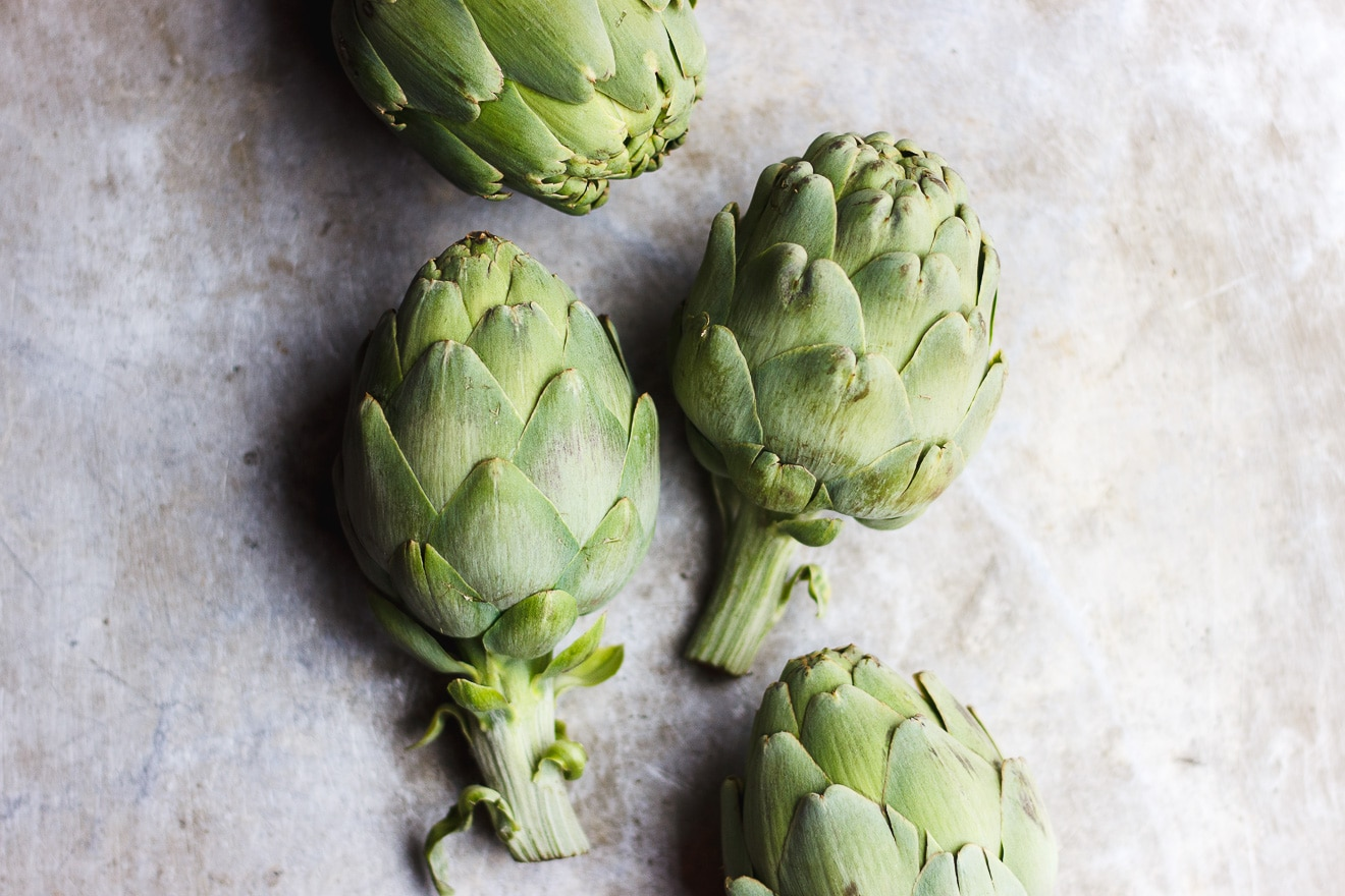 Easy Braised Artichokes with Lemon + Macadamia Nut Oil | Super easy stovetop braised artichokes summed in vegetable broth and dressed with fresh lemon juice and macadamia nut oil. Artichokes as an entree made easy. #artichokes #braisedartichokes