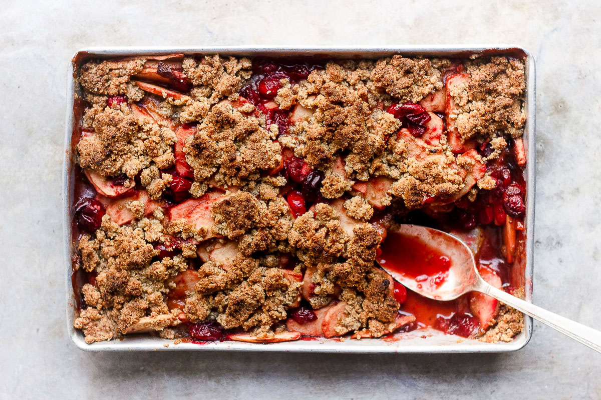 apple cranberry crisp in baking tray with spoon