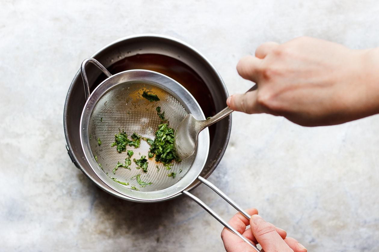 fresh mint simple syrup in a sieve