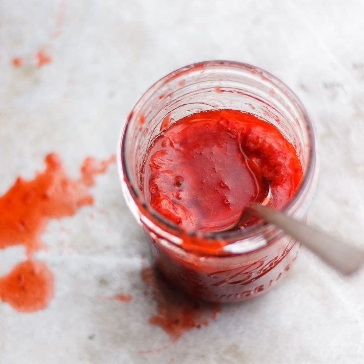 strawberry sauce in a jar with spoon