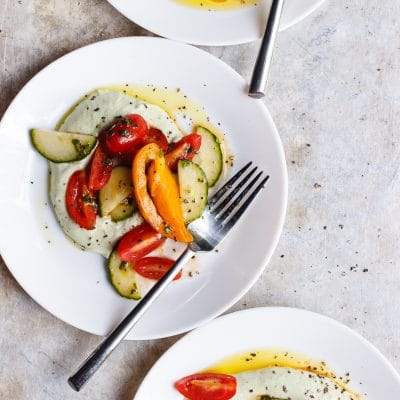 Basil Whipped Ricotta with Tomato Salad | A late summer tomato and cucumber salad on a bed of basil whipped ricotta. The best way to use up the bountiful end of summer produce.