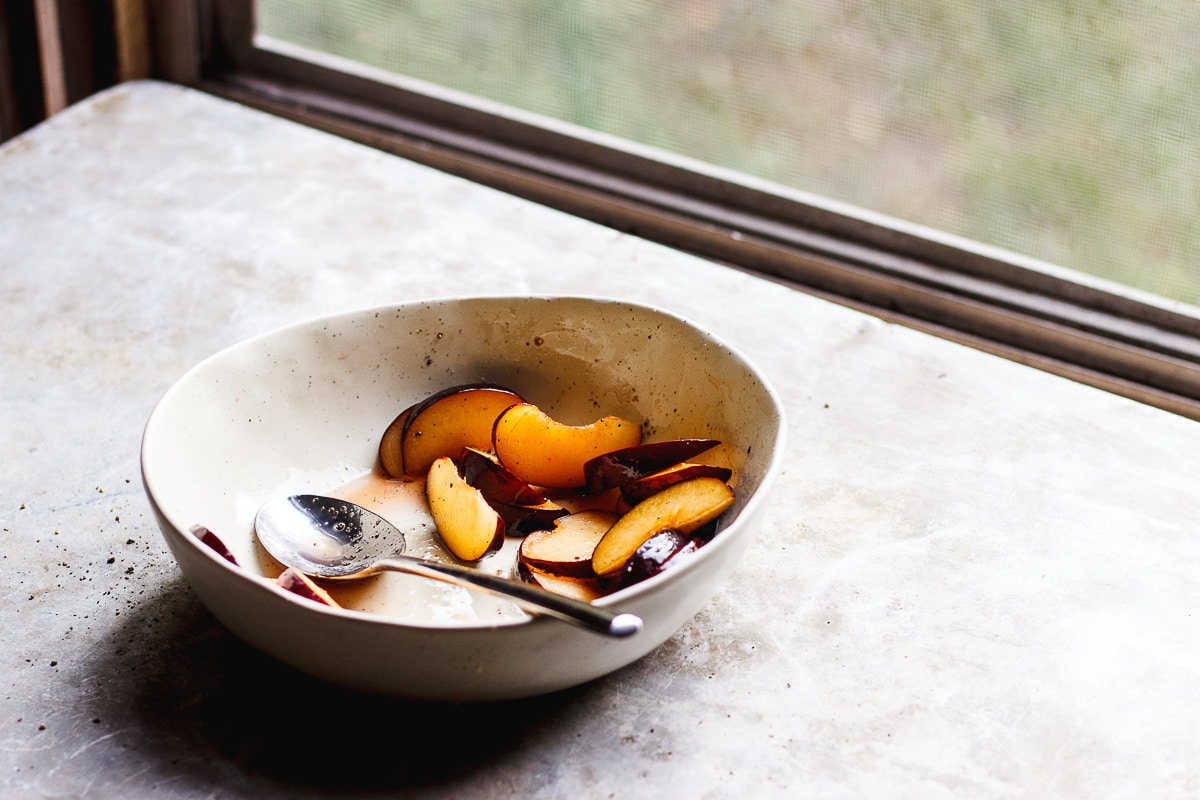 plums sliced in a bowl on a windowsill