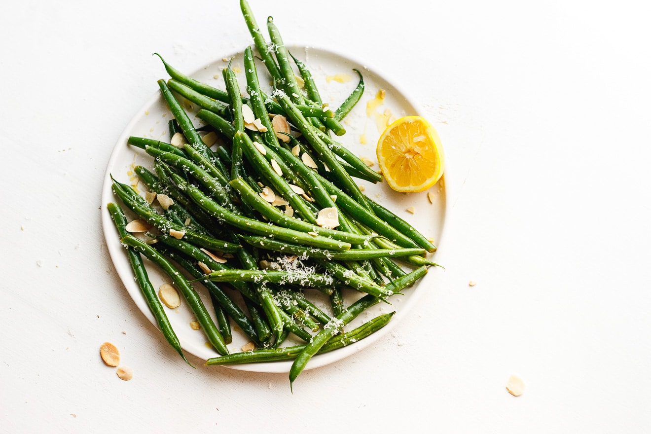 lemony green beans on a plate with toasted almonds and lemon