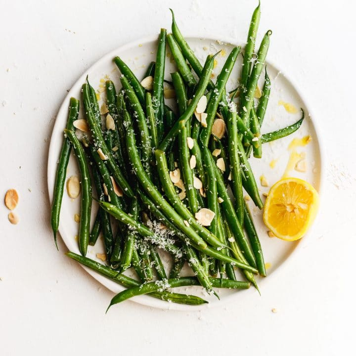 lemony green beans on a plate with toasted almonds and lemon and cheese