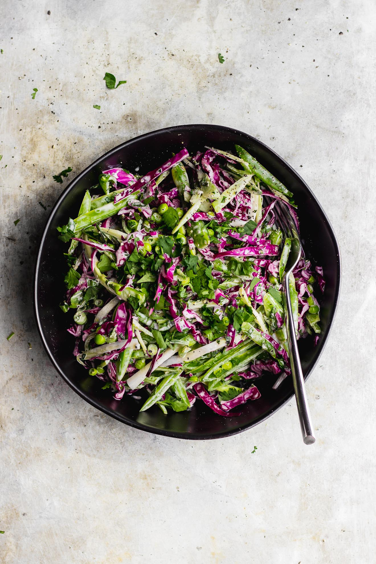 Broccoli Stem Slaw with Snap Peas + Basil Cilantro Aioli | A broccoli stem slaw with snap peas and red cabbage and an herby basil cilantro aioli. A vegan, gluten-free creamy broccoli stem slaw recipe. #broccolistemrecipes #herbyslaw