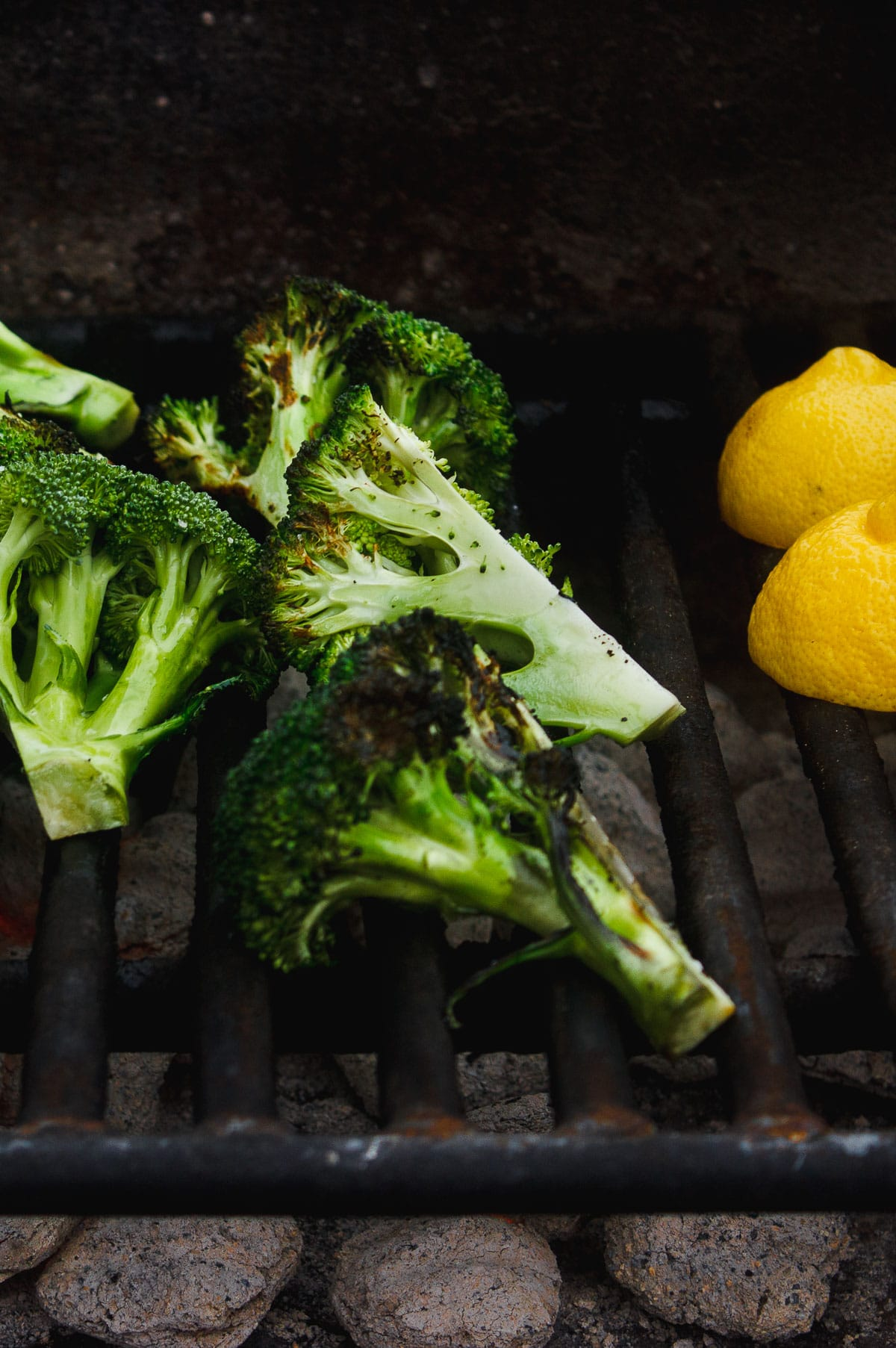 Grilled broccoli that is tossed in a zesty, charred lemon and parsley sauce. A vegan grilled side dish for anytime of year. #grilledbroccoli #grilledlemon #charredbroccoli