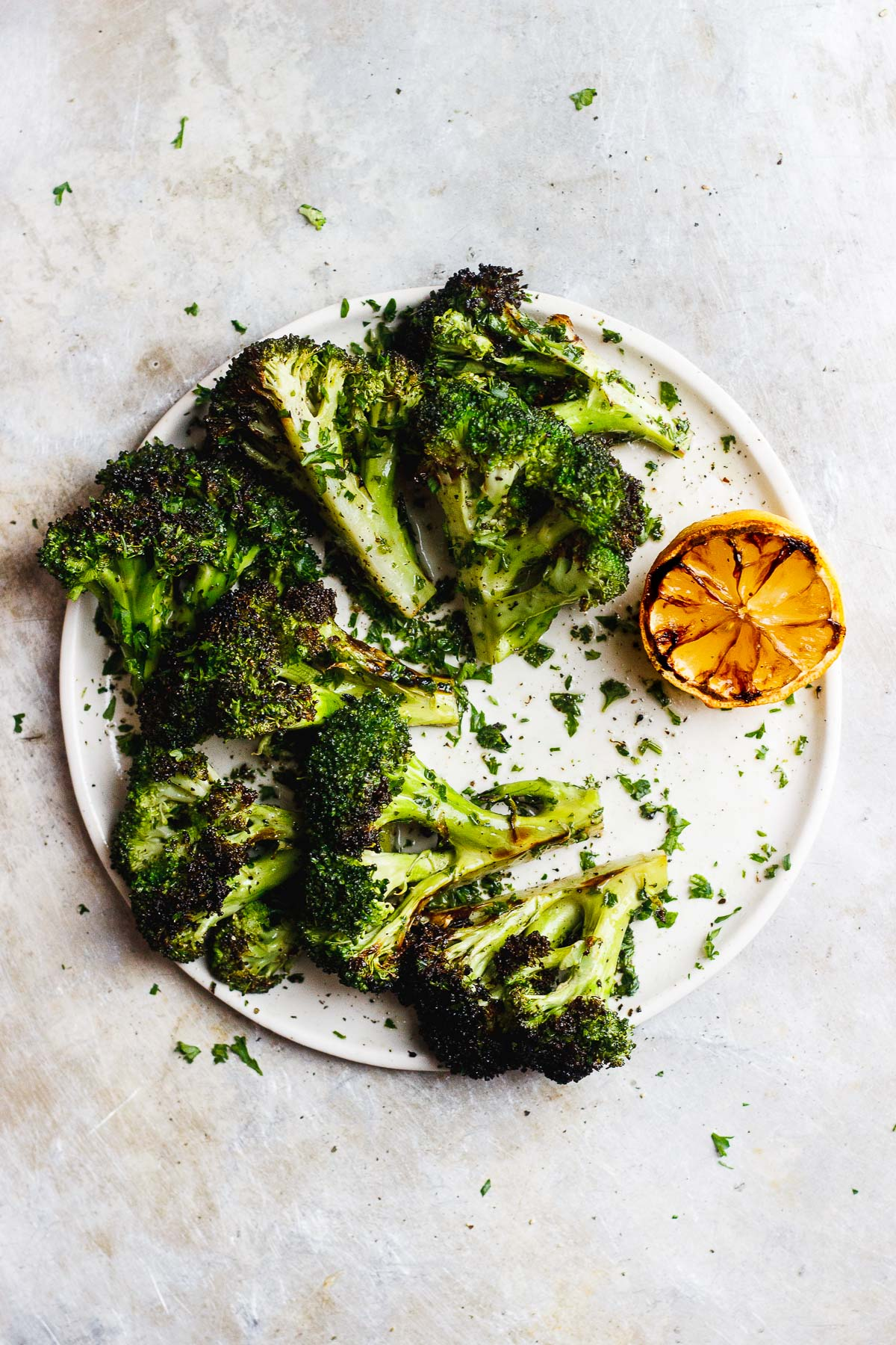Grilled broccoli that is tossed in a zesty, charred lemon and parsley sauce. A naturally vegan and gluten-free side dish. #grilledbroccoli #grilledlemon #charredbroccoli