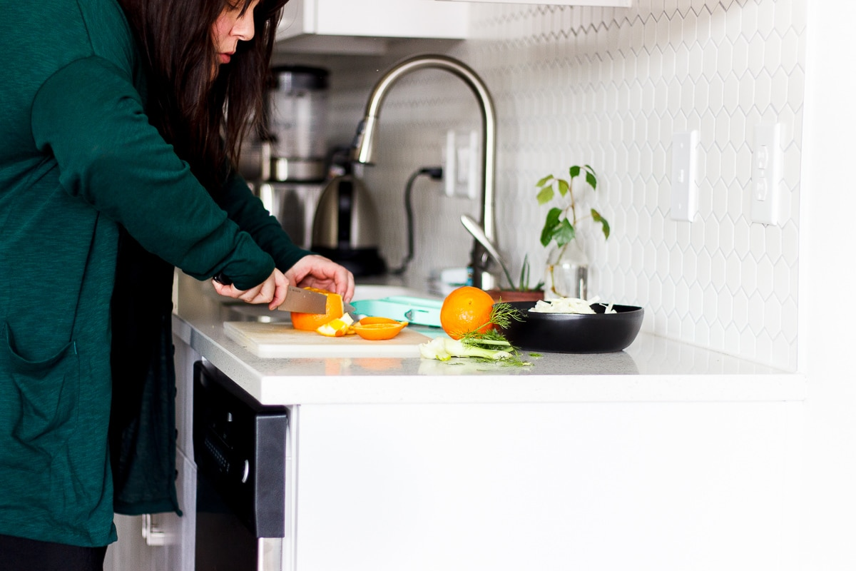 woman cutting an orange in a kitchen