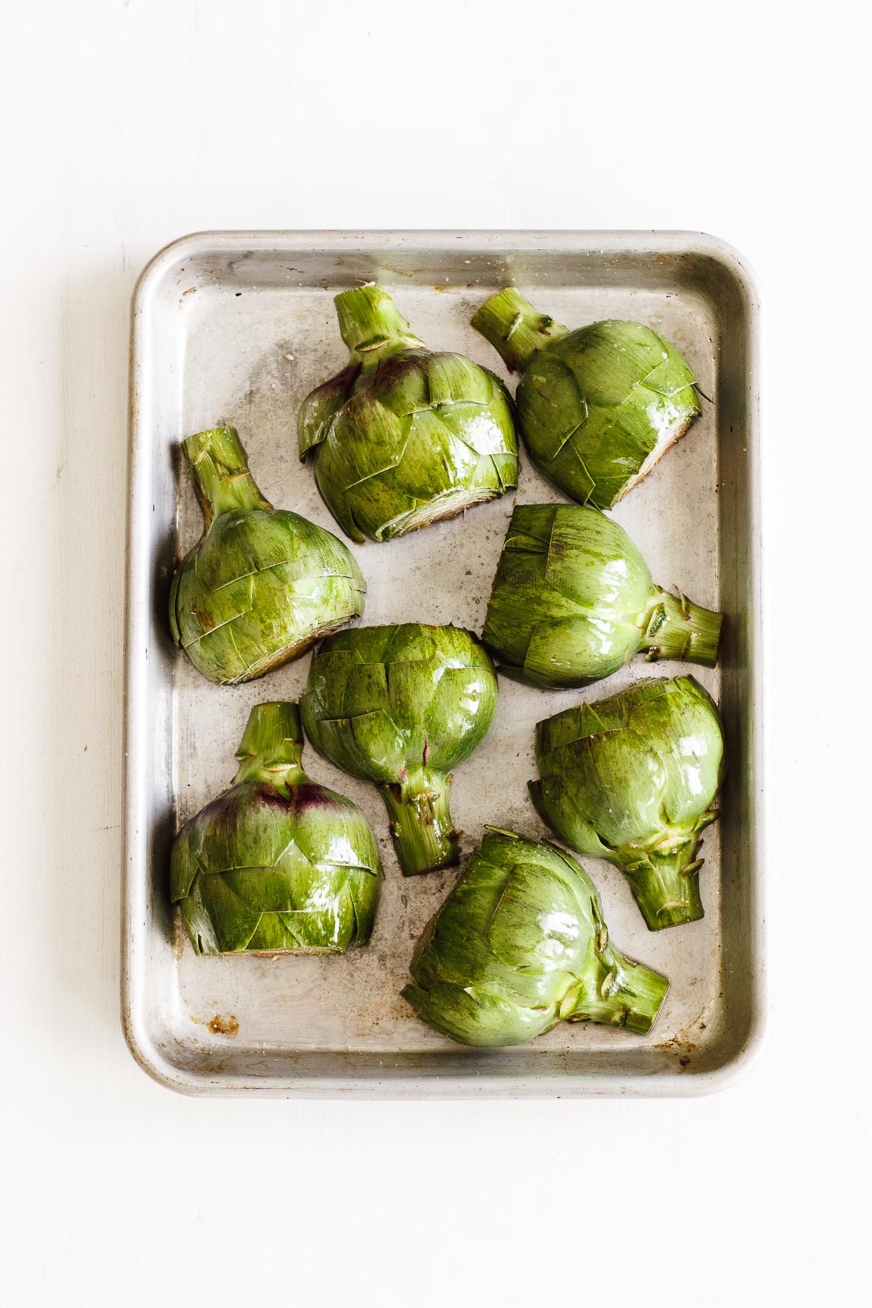 halved artichokes on a sheet pan
