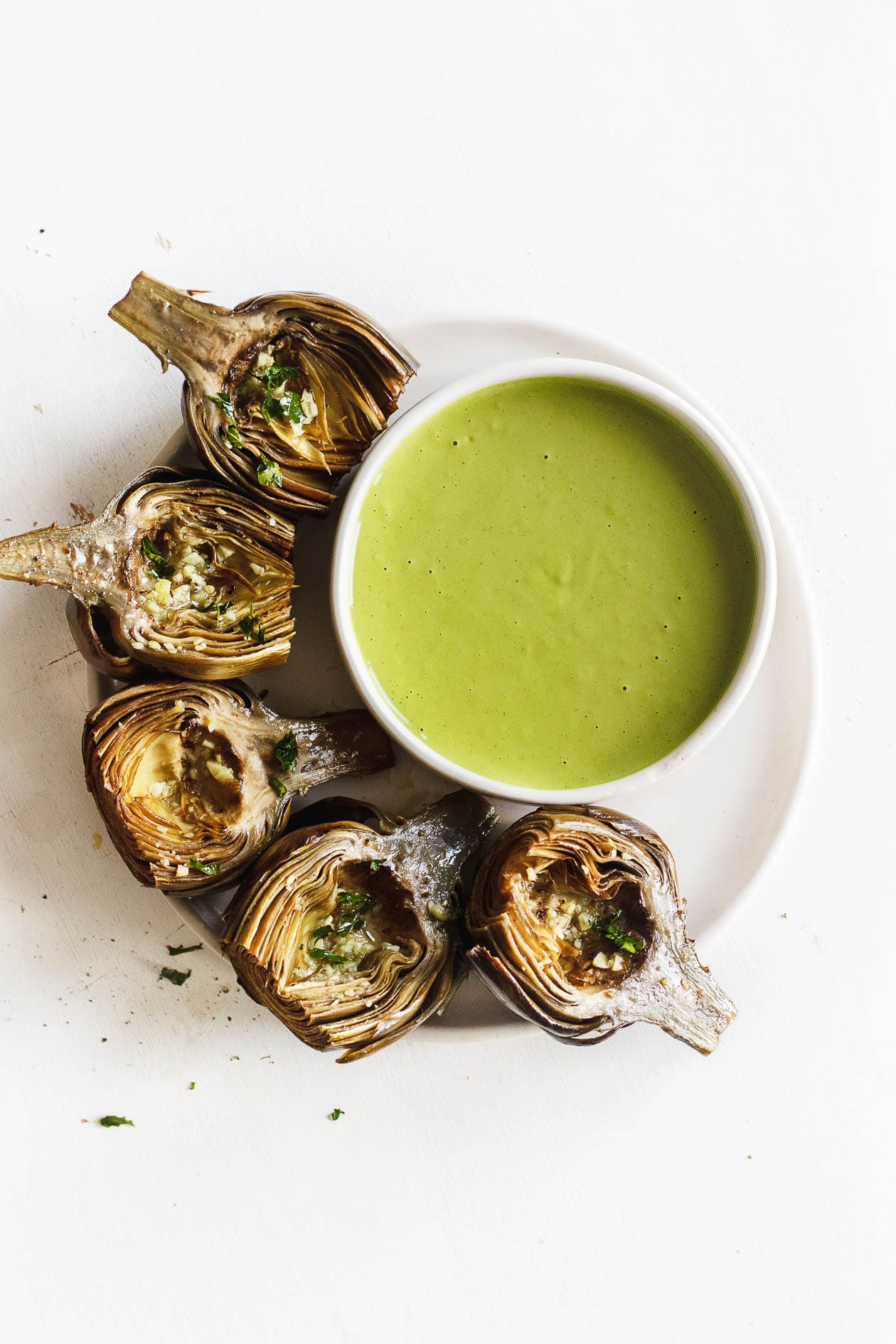 roasted artichokes on a plate with green goddess sauce