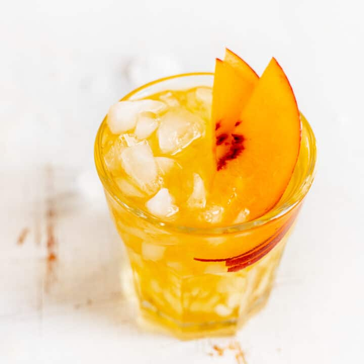 peach black tea spritzer with peach slices in glass